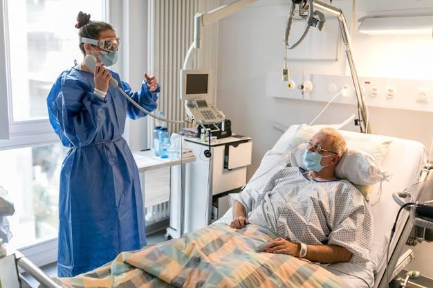 Pflegefachfrau Nora Tschanz benutzt das Telefon, um sich etwas bringen zu lassen, statt das Zimmer verlassen und sich umziehen zu müssen. Covid-Patient Roland Lerch trägt solange eine Hygienemaske.