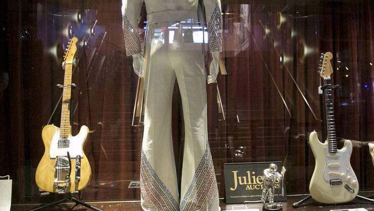 Auch sie wurden versteigert: Ein Bühnenkostüm von Pop-Sänger Elton John (m) und eine Gitarre (l), die Bob Dylan in einer entscheidenden Phase seiner Musik-Karriere begleitete. (Archiv)