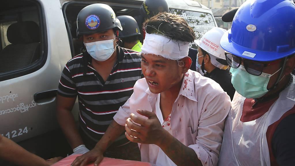 dpatopbilder - Männer begleiten einen verletzten Demonstranten. Die Polizei hatte versucht die Kundgebung, die sich gegen die Militärjunta in Myanmar richtete, aufzulösen. Foto: -/AP/dpa