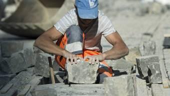 Ein Bauarbeiter verlegt Pflastersteine in Bern (Symbolbild)
