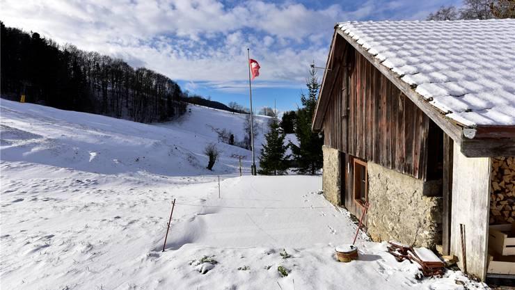 Bringt Einnahmen, auch wenn der Skilift (hinten im Bild) aus Schneemangel nicht in Betrieb ist: Skihütte mit Terrasse auf der Schafmatt in Oltingen am Freitagmittag.