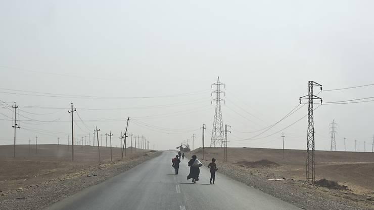 Aus ihren Dörfern vertriebene Menschen auf einer Strasse in der Nähe von Mossul.