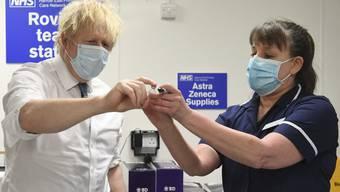 Der britische Premierminister Boris Johnson lässt sich den Oxford/Astrazeneca Impfstoff zeigen.