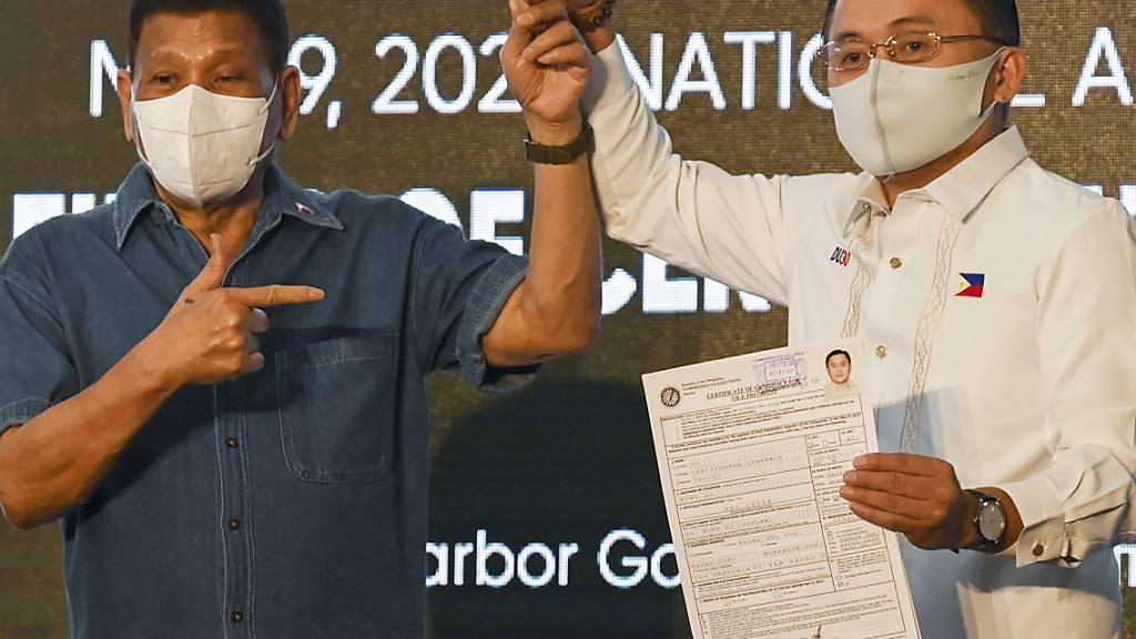Rodrigo Duterte (l) will künftig seinen langjährigen Berater Christopher Go unterstützen, der gerade seine Kandidatur für das Amt des Vizepräsidenten eingereicht hat. Foto: Lisa Marie David/POOL REUTERS/AP/dpa