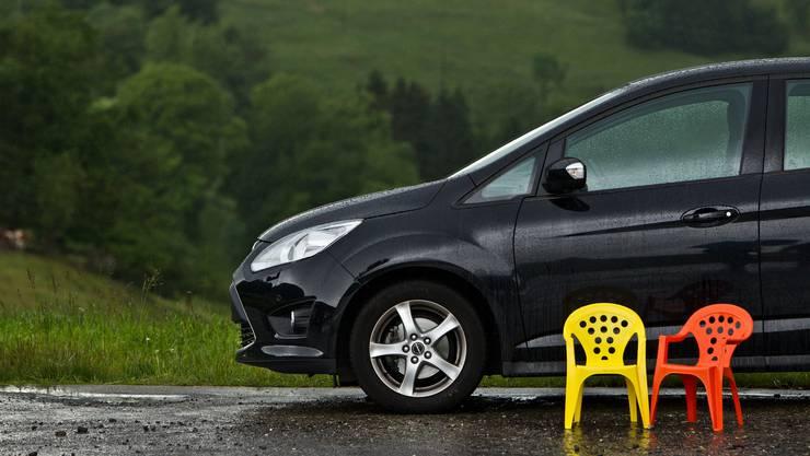 Zwei einsame und nasse Stühle neben einem Auto