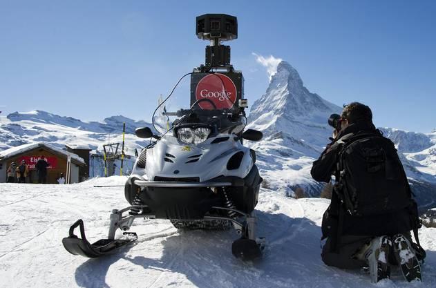 Ein Fotograf macht Bilder des Street View Schneemobils vor dem Matterhorn.