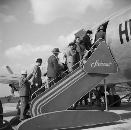 Die Passagiere besteigen ein Swissair-Flugzeug, dass den Zürcher Flughafen zum ersten Mal Richtung London verlassen wird.