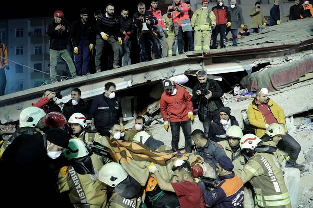 Rettungskräfte tragen ein Opfer aus den Trümmern.