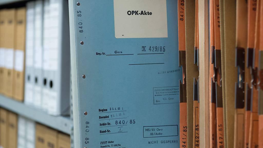 ARCHIV - Eine Stasi-Akte mit der Aufschrift OPK-Akte (Operative Personenkontrolle) steckt in der BStU-Außenstelle in Gera (Thüringen) in einem Regal. Foto: Sebastian Kahnert/dpa-Zentralbild/dpa