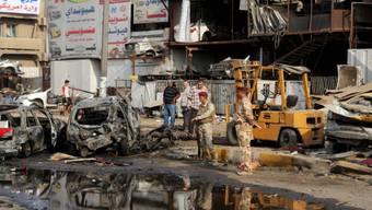 Sicherheitskräfte inspizieren den Ort, an dem eine Bombe hochging