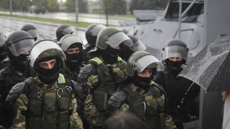 Bereitschaftspolizisten in schwerer Montur blockieren während eines Protests von Unterstützern der belarussischen Opposition eine Straße zum Palast der Unabhängigkeit in Minsk. Foto: -/AP Photo/TUT.by/dpa