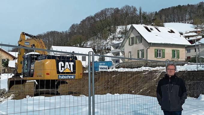 Die Einfamilienhäuser rechts und links des Baggers müssen dem Neubau weichen. Letzteres hat das Bauprojekt um Jahre verzögert.