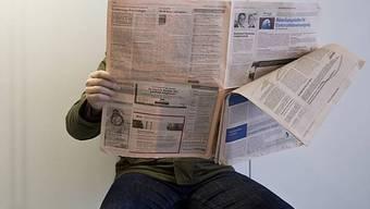 Ein Mann schaut die Stelleninserate in der Zeitung an (Symbolbild)