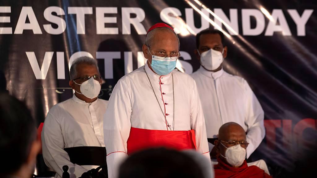 Kardinal Malcolm Ranjith (M), Erzbischof von Colombo, hält in der St. Anthony's Church während zwei Schweigeminuten in Gedenken an die Opfer der Anschläge vom Ostersonntag 2019 inne. Foto: Eranga Jayawardena/AP/dpa