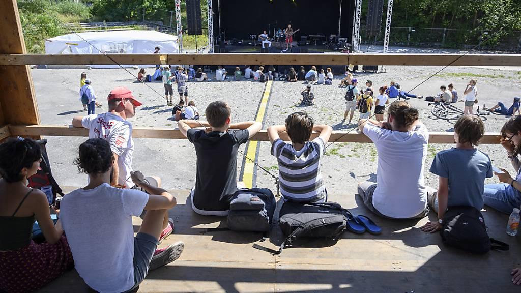 Kilmafestival auf der Hardturmbrache in Zürich: Besucherinnen und Besucher schauen bei einem Konzern zu.