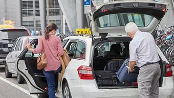 Ein Taxichauffeur im Pensionsalter hilft einer Kundin. (Archivbild)