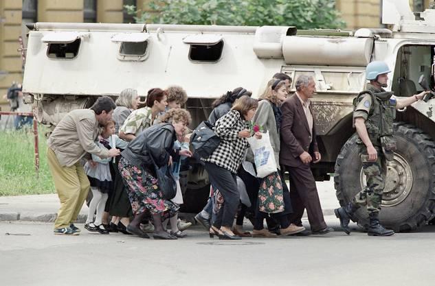 Einwohner von Sarajevo gehen hinter einem gepanzerten Wagen der französischen Blauhelme in Deckung. 1995.