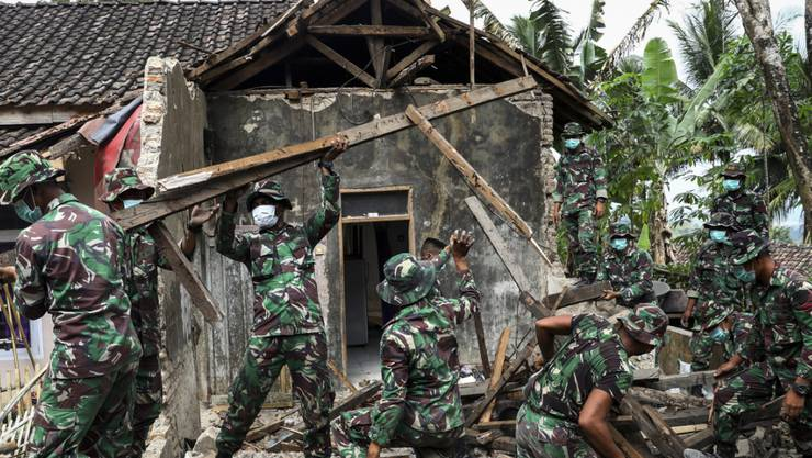Beträchtliche Schäden und Tote nach dem Erdbeben: Einsatzkräfte inspizieren die Schäden an einem Haus in Mandalawangi auf Java.