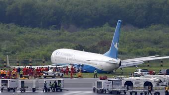 Über die Landebahn hinaus gerutscht: Die Maschine der chinesischen Fluggesellschaft Xiamen Airlines liegt nach der missglückten Landung neben der Piste im Gras.