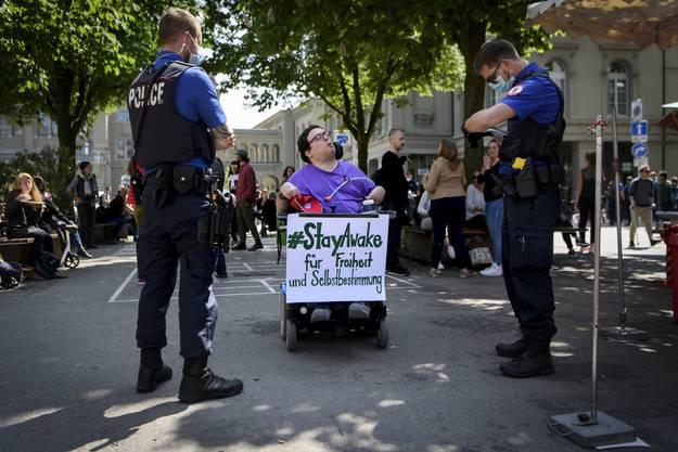 Eine Person im Rollstuhl spricht mit der Polizisten, bei einer Demonstration gegen den Coronavirus Lockdown, am Samstag, 16. Mai 2020, im Baerenplatz, in Bern. (KEYSTONE/Anthony Anex)