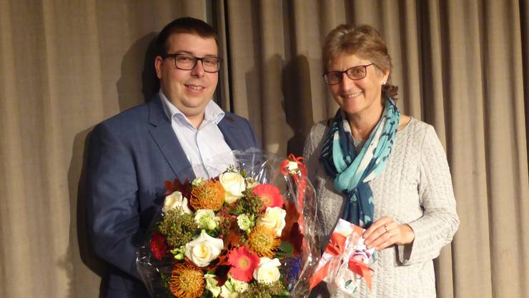 Bürgergemeindepräsident Patrick Friker übergibt Verwalterin Silvia Meier-Köppel einen Blumenstrauss für 25 Dienstjahre.
