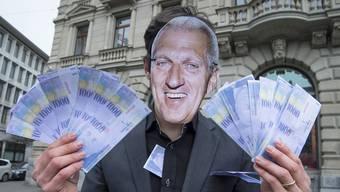 Ein Vollgeld-Aktivist mit einer Pierin Vincenz-Maske hält gedruckte Tausender Noten in der Hand, anlässlich einer Aktion zur Causa «Vincenz Raiffeisen».