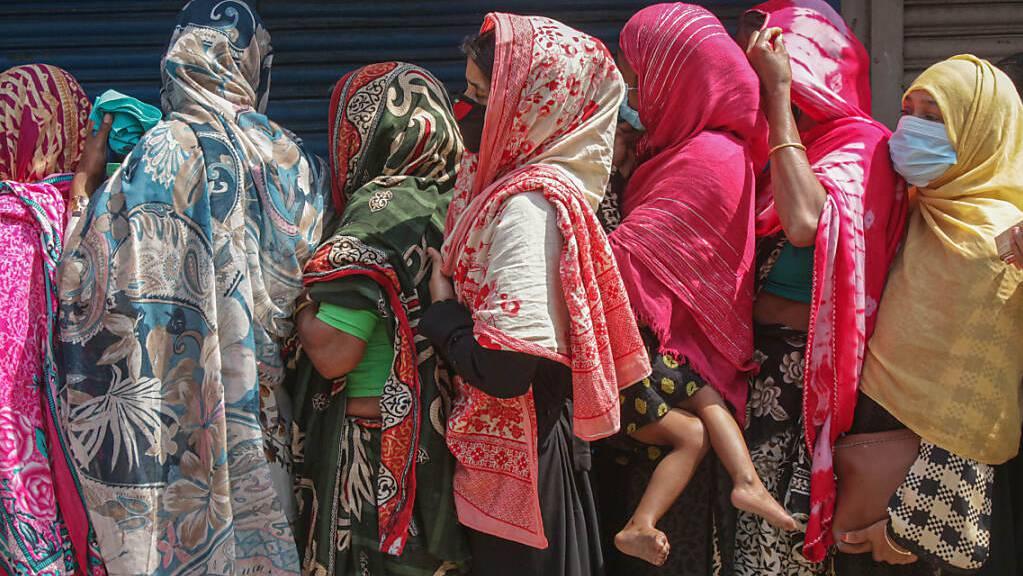 Frauen stehen gedrängt in einer Schlange, um Reis und Mehl auf dem offenen Markt zu kaufen. Ein landesweiter Lockdown hat für sieben Tage begonnen. Foto: Md Rafayat Haque Khan/ZUMA Wire/dpa