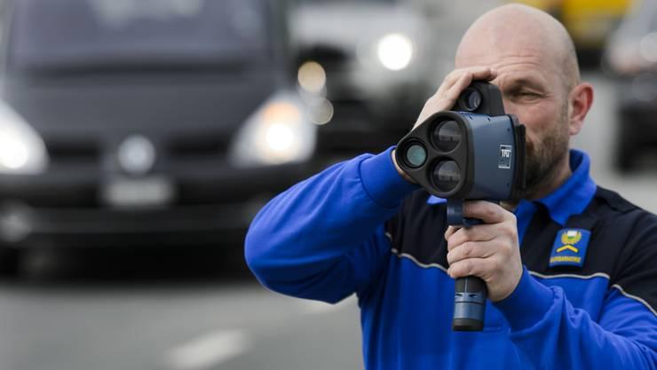 Ein Polizist misst mit einem Lasermessgerät Fahrzeuge.