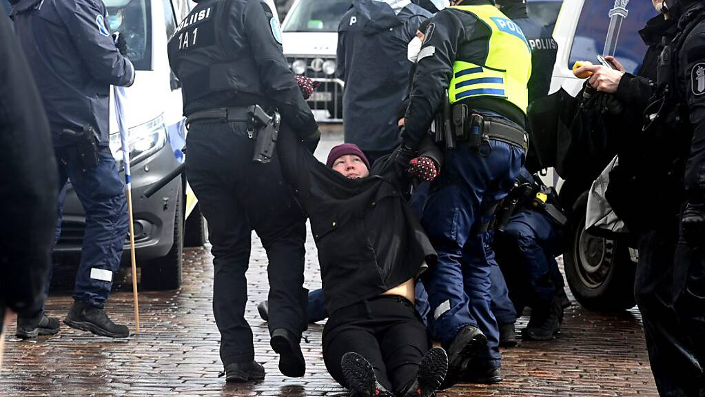 Zwei Polizisten tragen einen Protestteilnehmer weg. Foto: Heikki Saukkomaa/Lehtikuva/dpa