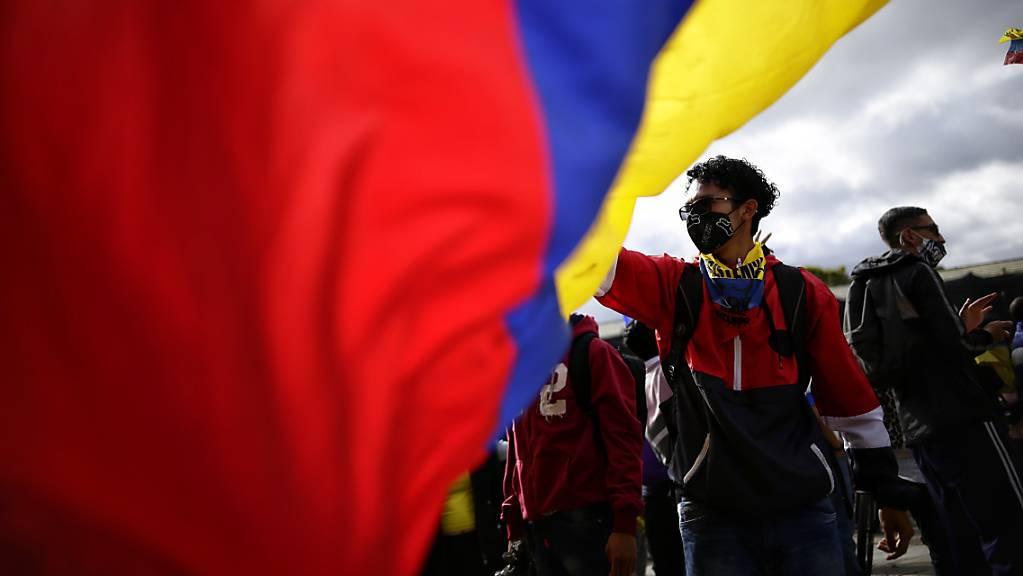 Junge Demonstranten schwenken eine riesige Fahne von Kolumbien während eines neuen Protests gegen die Regierung von Präsident Duque inmitten der Corona-Pandemie.