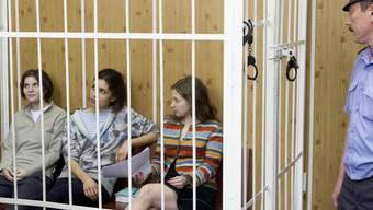Die drei Musikerinnen vor Gericht in einem Gitter