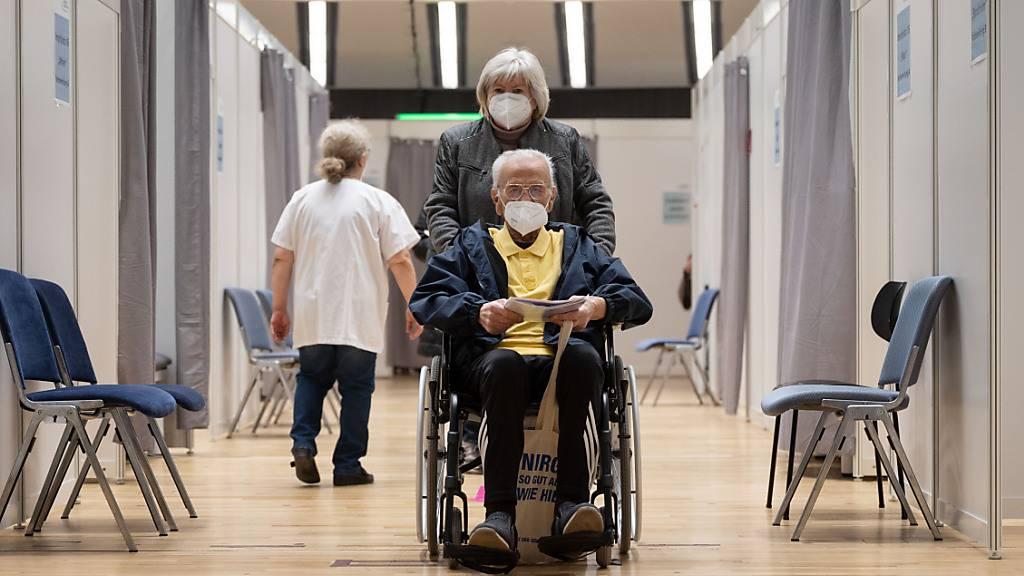 Ein Impfling wird nach seiner Impfung im Rollstuhl durch einen Gang des Impfzentrums des Klinikum Stuttgart geschoben. Foto: Marijan Murat/dpa