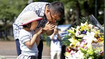 Ein Mann und seine Tochter beten für die Opfer des amerikanischen Atombombenabwurfs vor 75 Jahren. Foto: Takuto Kaneko/Kyodo News/AP/dpa