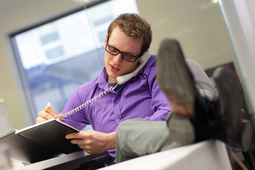 young caucasian businessman on phone - bad sitting posture