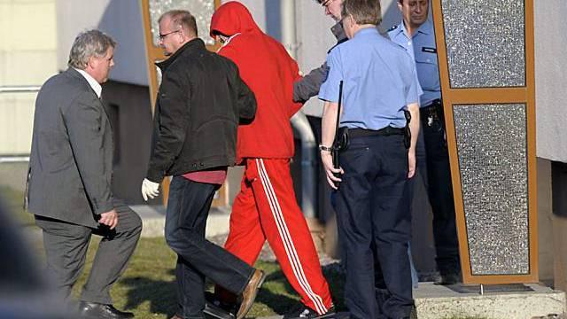 Der mutmassliche Täter (rot gekleidet) wird abgeführt