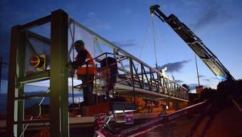 Weil der Verkehr nachts weniger behindert wird, schrauben die Arbeiter in Dunkeln am Stahlträger.