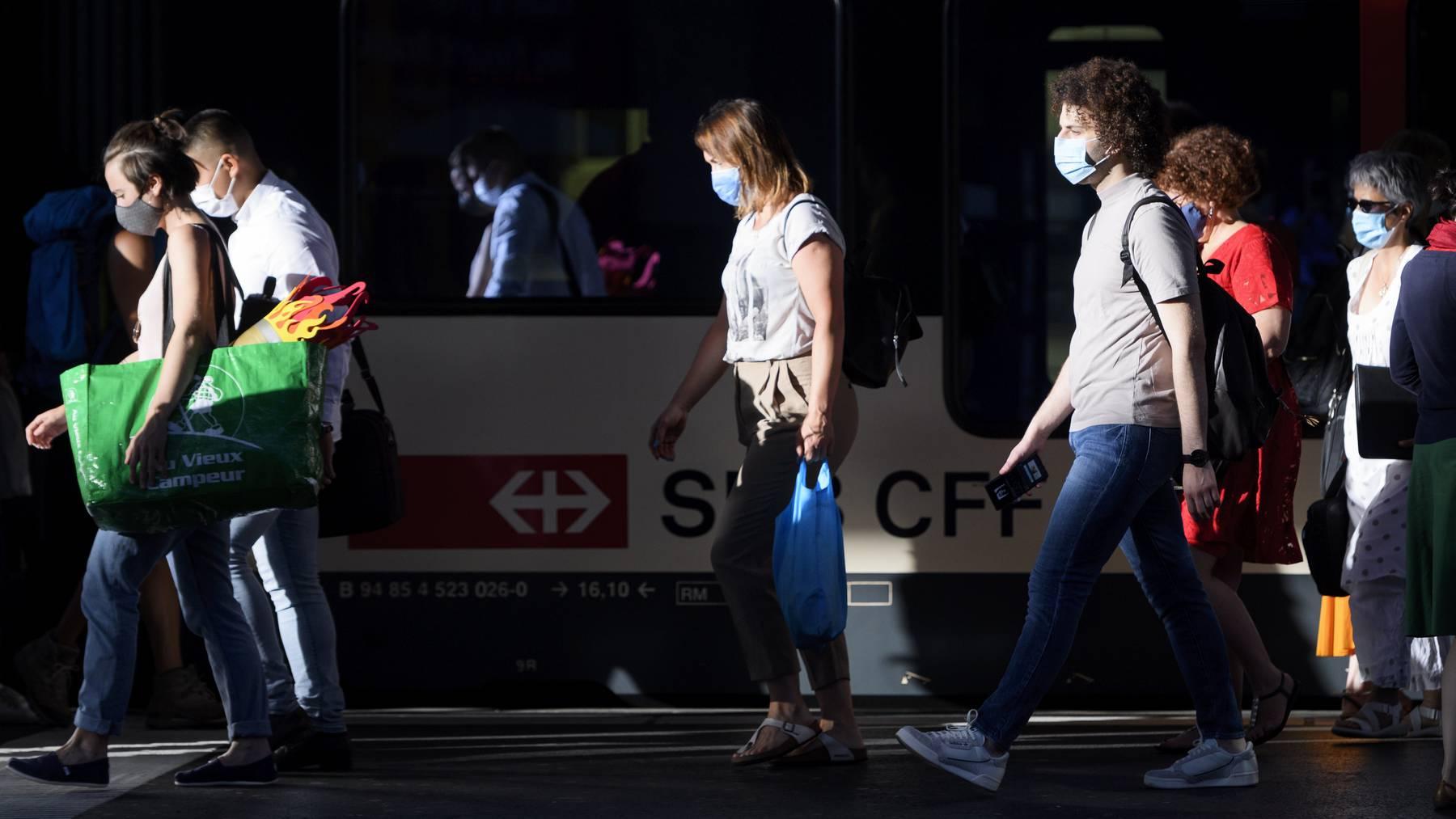 Zugpassagiere mit Masken am Bahnhof in Lausanne