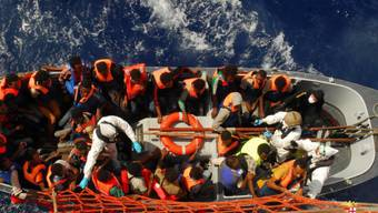 Von der italienischen Marine gerettete Flüchtlinge werden auf ein grössere Schiff gebracht. (Archiv)