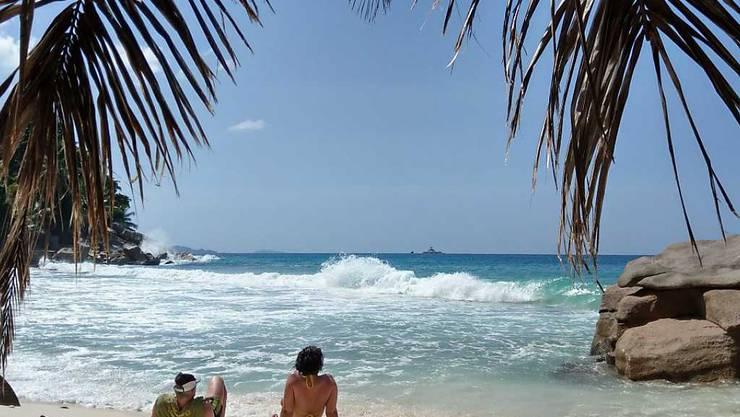 ARCHIV - Touristen liegen am Strand der Seychelleninsel La Digue. Foto: Sabrina Hentschel/dpa