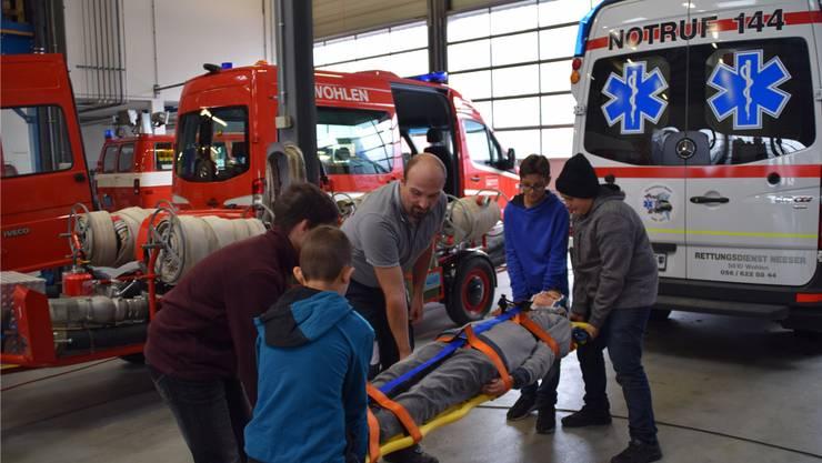 Rettungssanitäter Markus Woppmann zeigt den Kindern, wie man einen Verletzten fachgerecht abtransportiert.