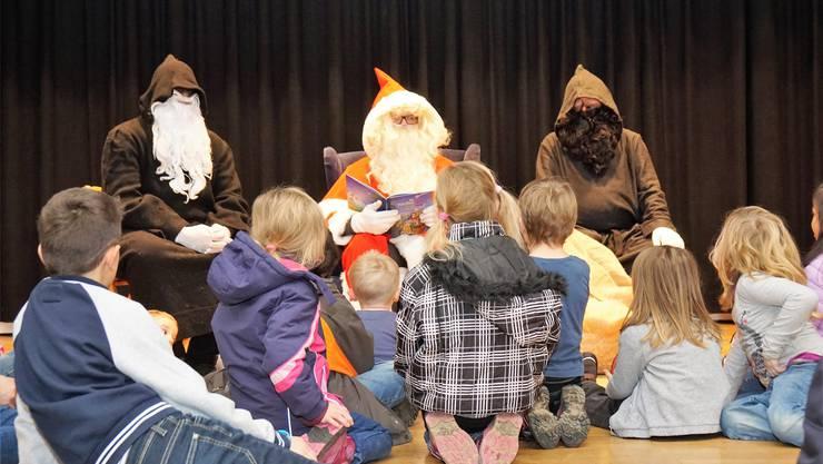 Gespannt lauschen die Kinder auf der Bühne den Geschichten von Samichlaus. sih
