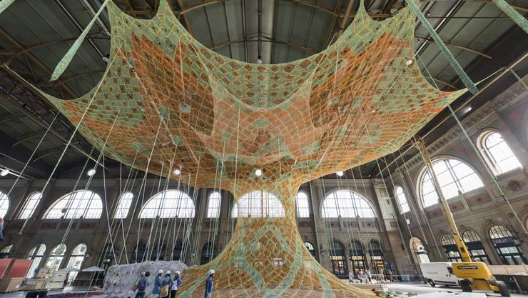 Ernesto Netos Baum aus gehäkelten Stoffstreifen im Hauptbahnhof Zürich. Der Künstler will den Menschen damit Freude bereiten und ihnen einen Ort der Ruhe schenken.