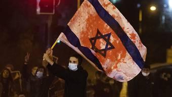 Ein Jugendlicher schwenkt bei einer Demonstration gegen die Polizei eine israelische Flagge, die mit roter Farbe beschmiert ist. Foto: Ariel Schalit/AP/dpa