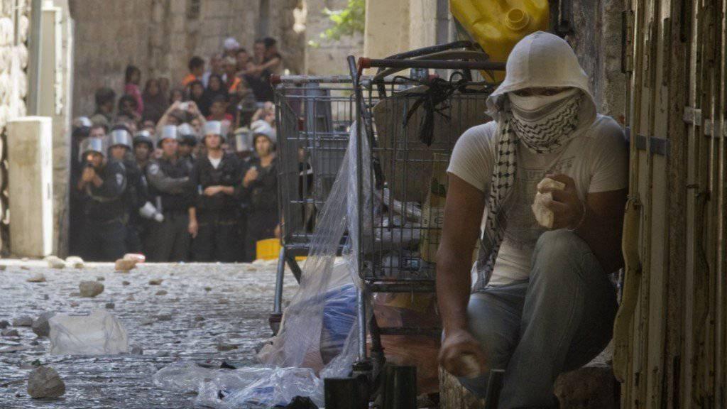 Ein palästinensischer Jugendlicher versteckt sich nach Steinwürfen gegen israelische Polizisten. (Archiv)