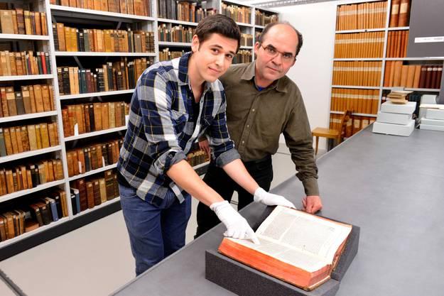 Der Archivleiter Guy Thomas (rechts) zeigt stolz eine der Trouvaillen aus dem Archiv der Basler Mission und der Mission 21.