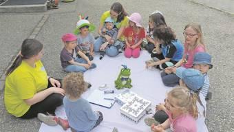 Die Kita-Kinder sind so viel wie möglich an der frischen Luft. Hier mit der Leiterin Saskia Scheidegger (mit Kind auf dem Schoss) und Michelle Salzmann, Lernende im 1. Lehrjahr als Fachbetreuerin Kind (FaBeK).