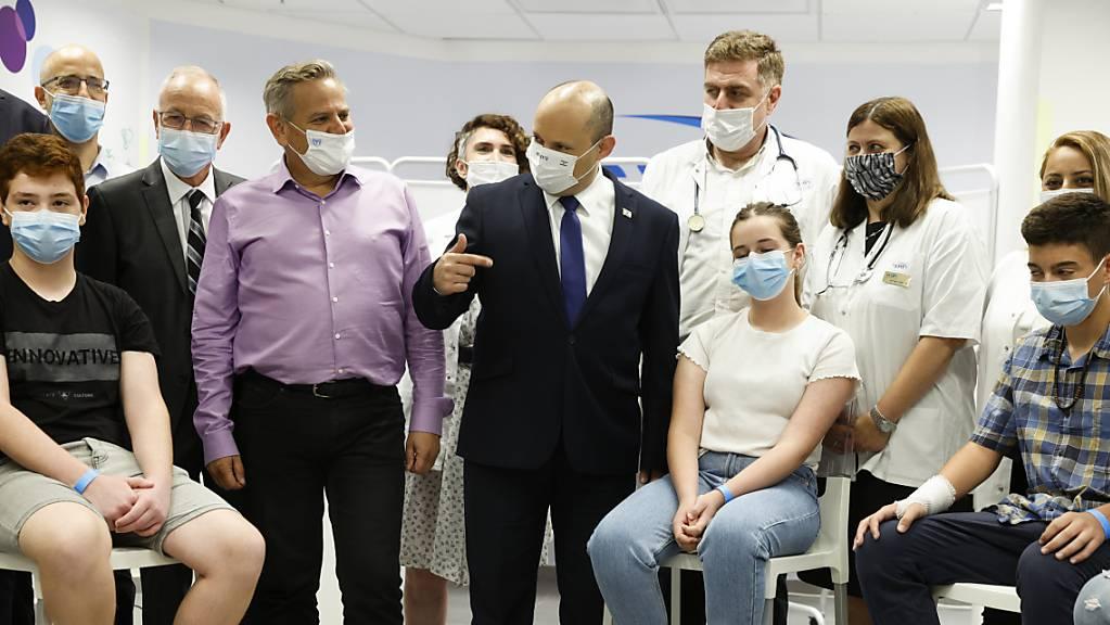 Naftali Bennett (M), Ministerpräsident von Israel, beim Besuch einer Maccabi Healthcare Maintenance Organisation (HMO), die Impfungen gegen das Coronavirus anbietet. Foto: Amir Cohen/Reuters Pool/AP/dpa