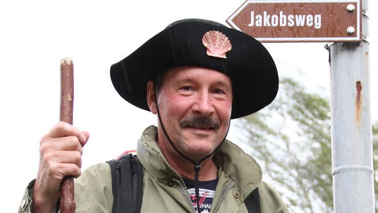 René Rohr steht in Jakobsweg-Vollmontur in seinem Garten. Hut und Rucksack sind Spezialanfertigungen. Robert Benz