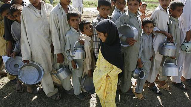 Kinder in Pakistan stehen für Wasser an