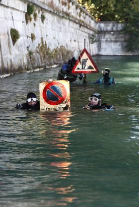 Taucher fischen Verkehrsschilder aus der Aare